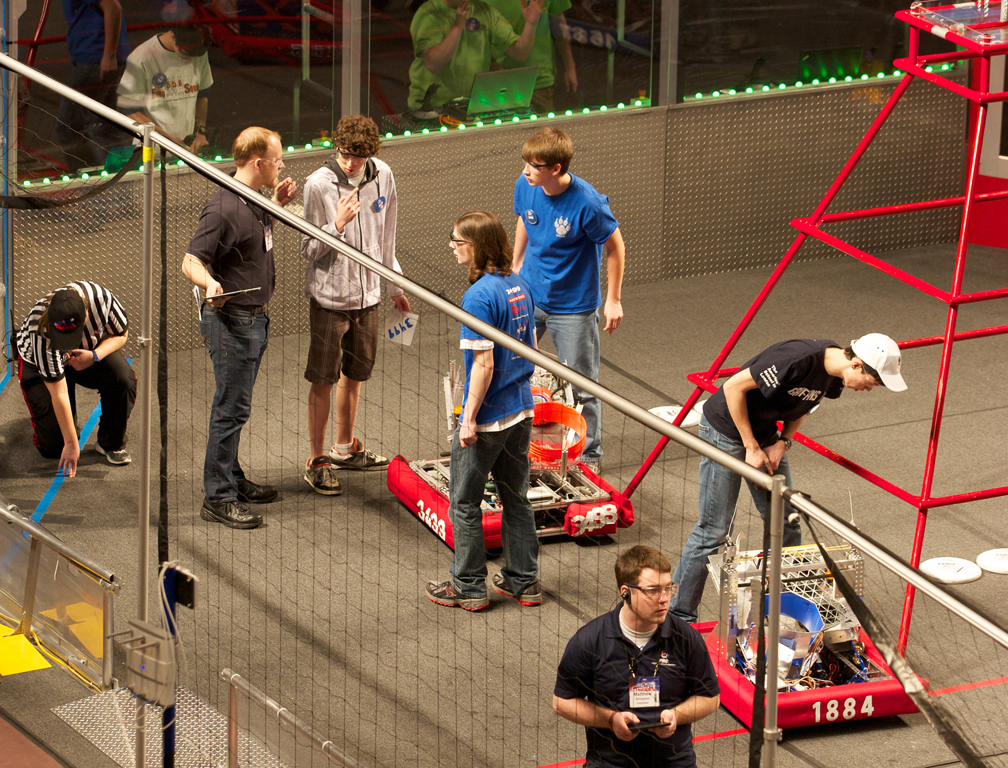 High school students discuss their plans over their robot at a FIRST Robotics meet