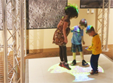 Three children examine a photo of the moon projected onto the floor