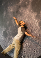 A student embraces a large-scale photo of the lunar surface mounted on the wall