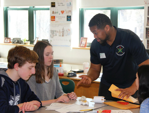 Two students are mentored by an adult volunteer from the National Society of Black Engineers