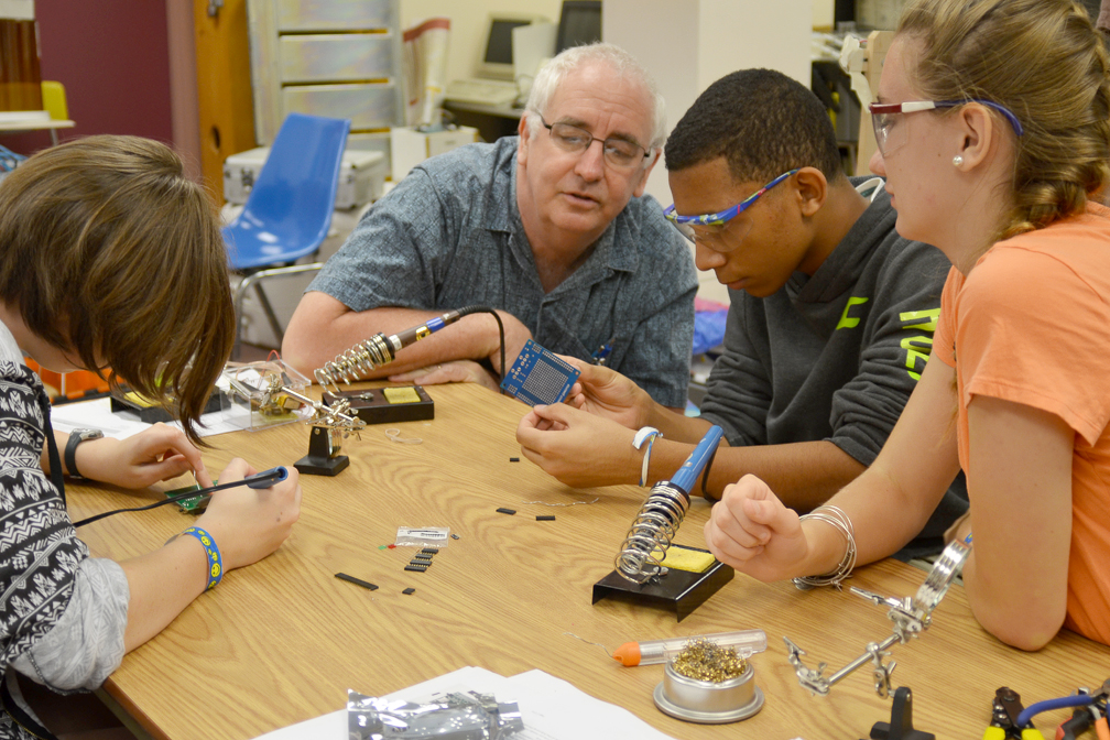 High school students from Project Smart work with an adult mentor on an electronics project