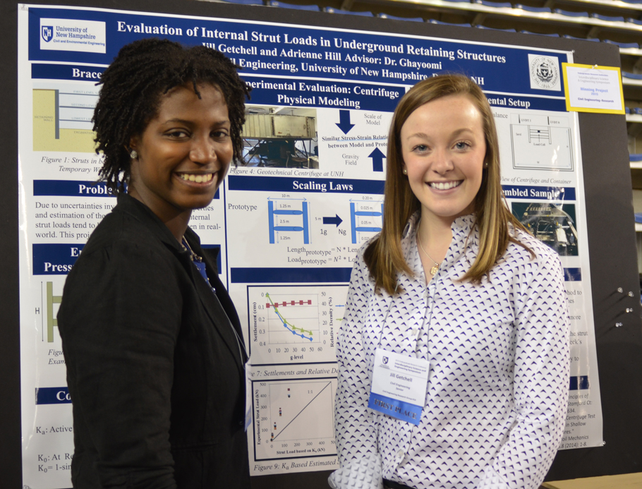 Two women stand in front of a research project poster at the Undergraduate Research Conference at UNH